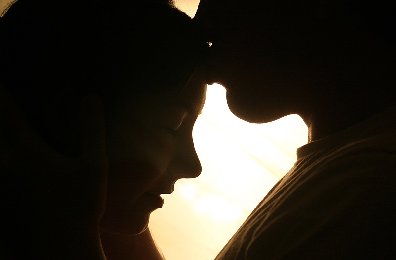 A man kisses a woman's forehead.