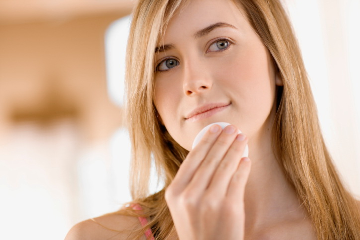 Teenage girl wiping chin with cosmetic pad