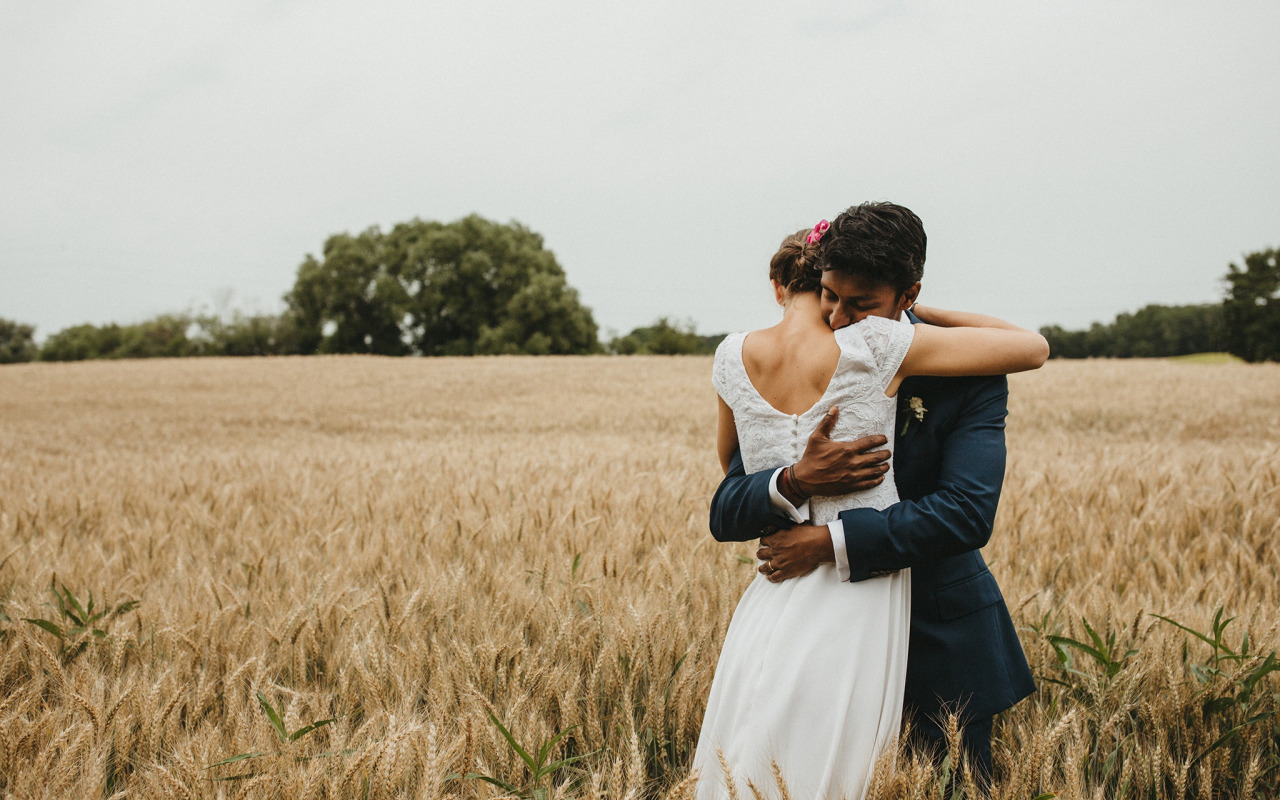 bride-groom-hug-wedding-dress-wheat-field-cloudy-countryside