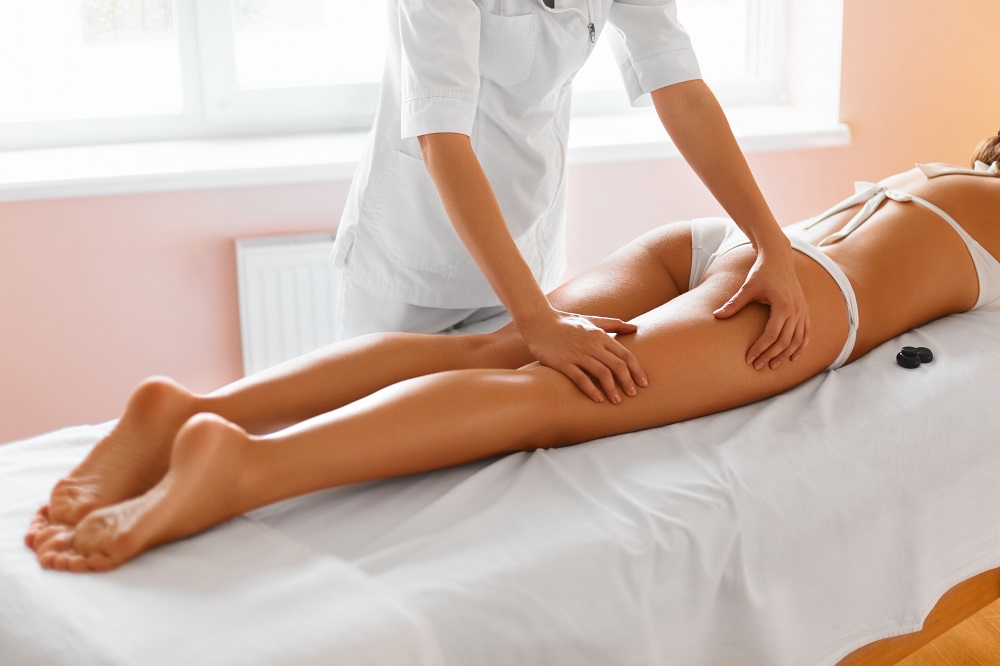 Spa woman. Body care. Close-up of beautiful long tanned woman legs receiving massage in spa salon. Skin care, wellbeing, wellness concept. Anti-cellulite spa treatment.