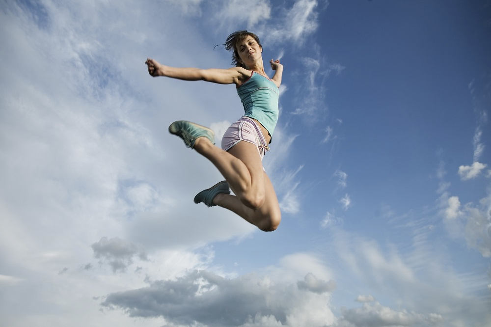 Young girl jumps into blue sky