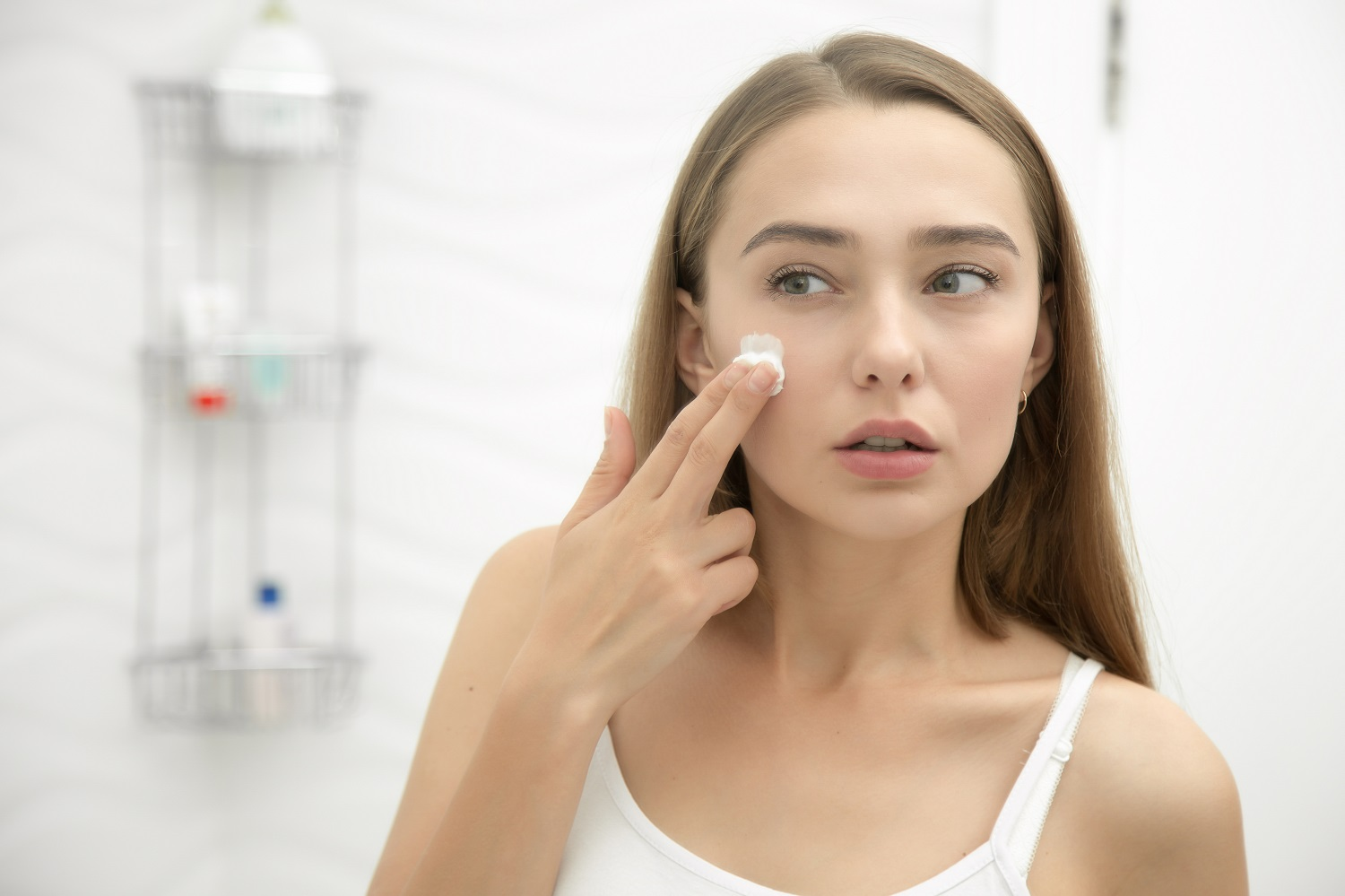 Young beautiful woman applying cream to her face and looking worried at the mirror at home bathroom. Beauty, skin care concept, lifestyle