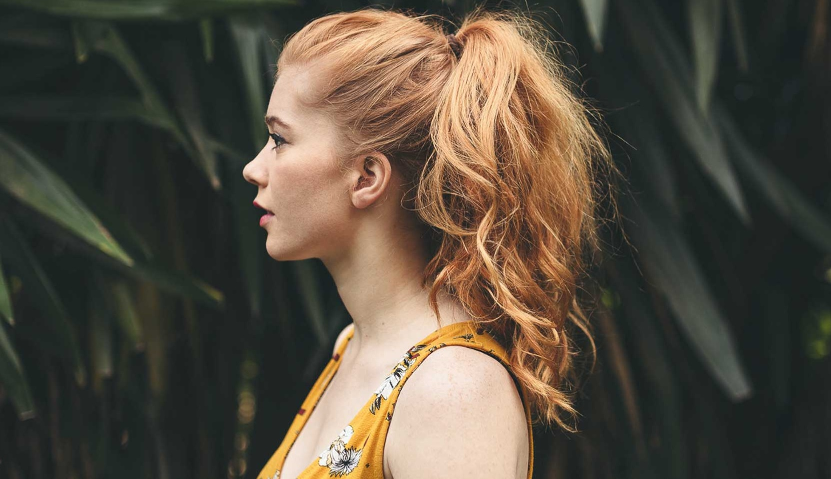 Profile view of a redhead woman among trees