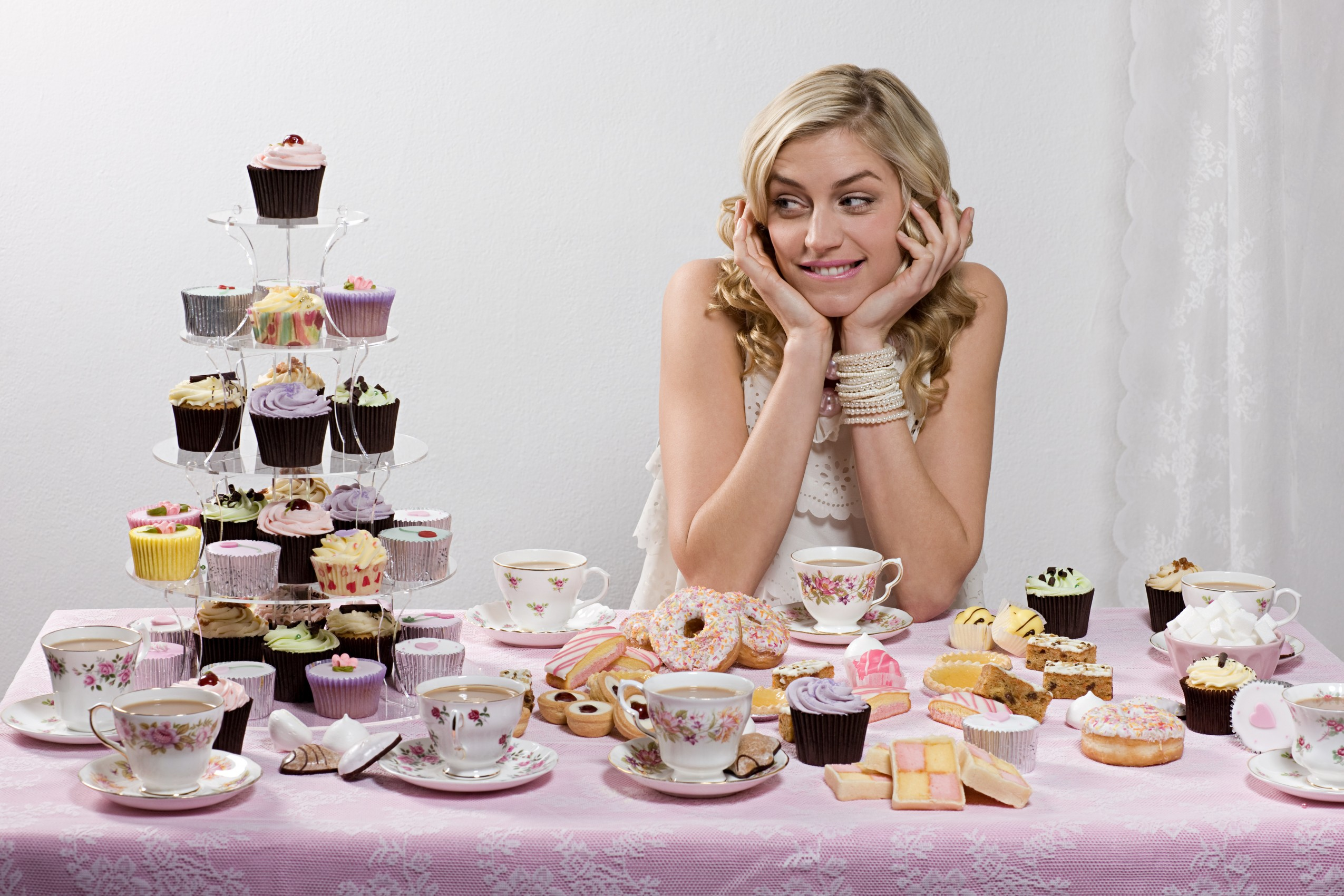 Woman with table of tea and cakes --- Image by © Ocean/Corbis