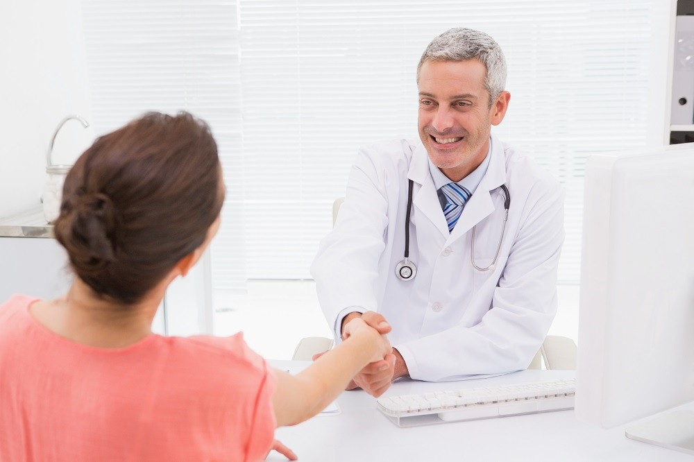Happy doctor handshake at his patient in medical office