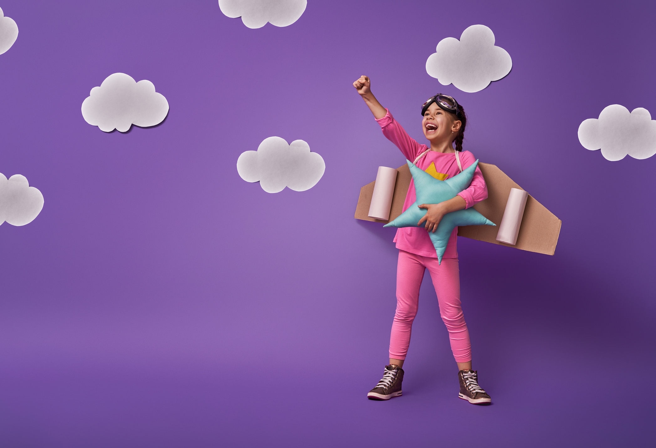 Little child girl in an astronaut costume is playing and dreaming of becoming a spaceman. Portrait of funny kid on a background of ultraviolet wall with white clouds.