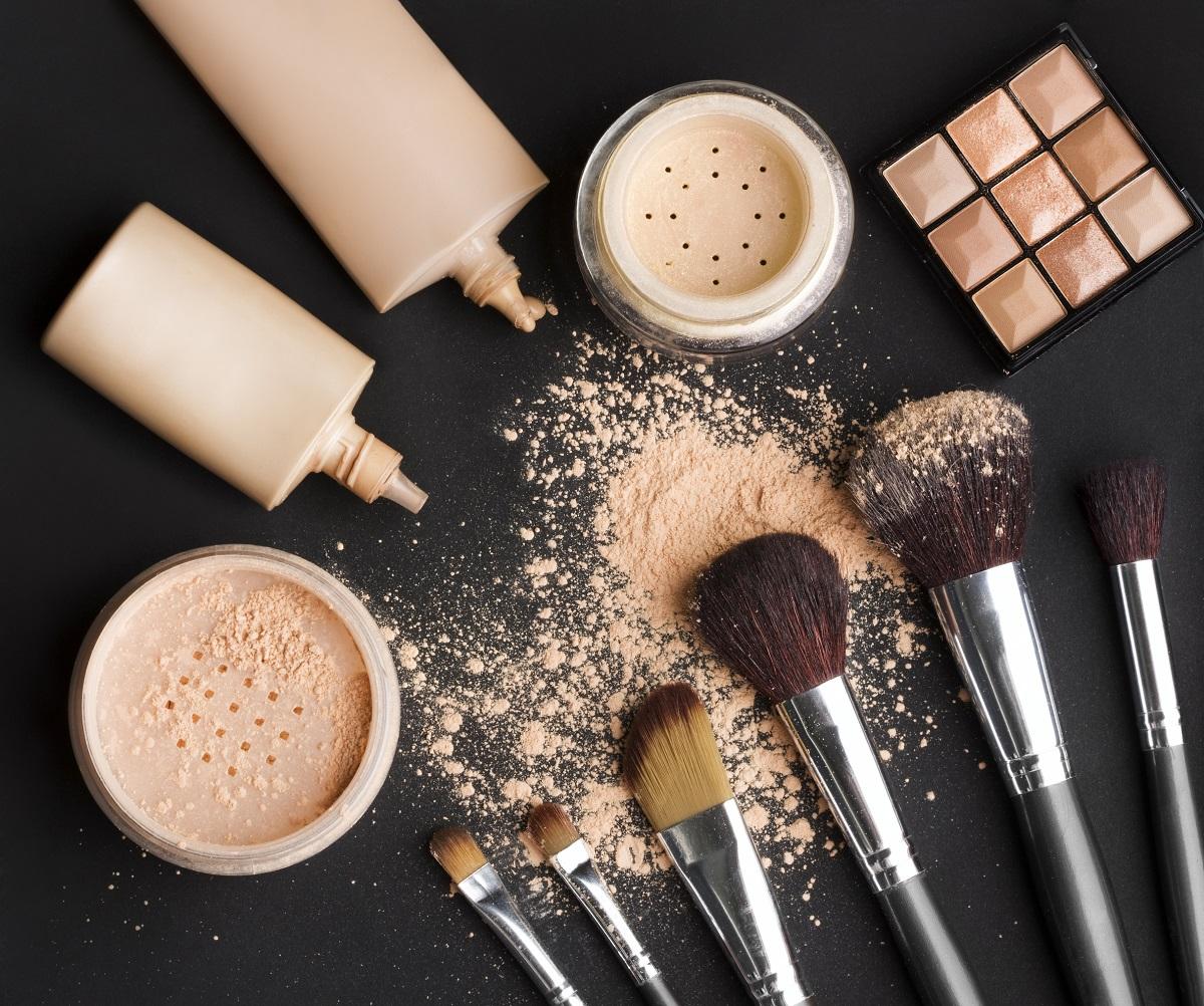 brushes, powder, makeup foundation on black