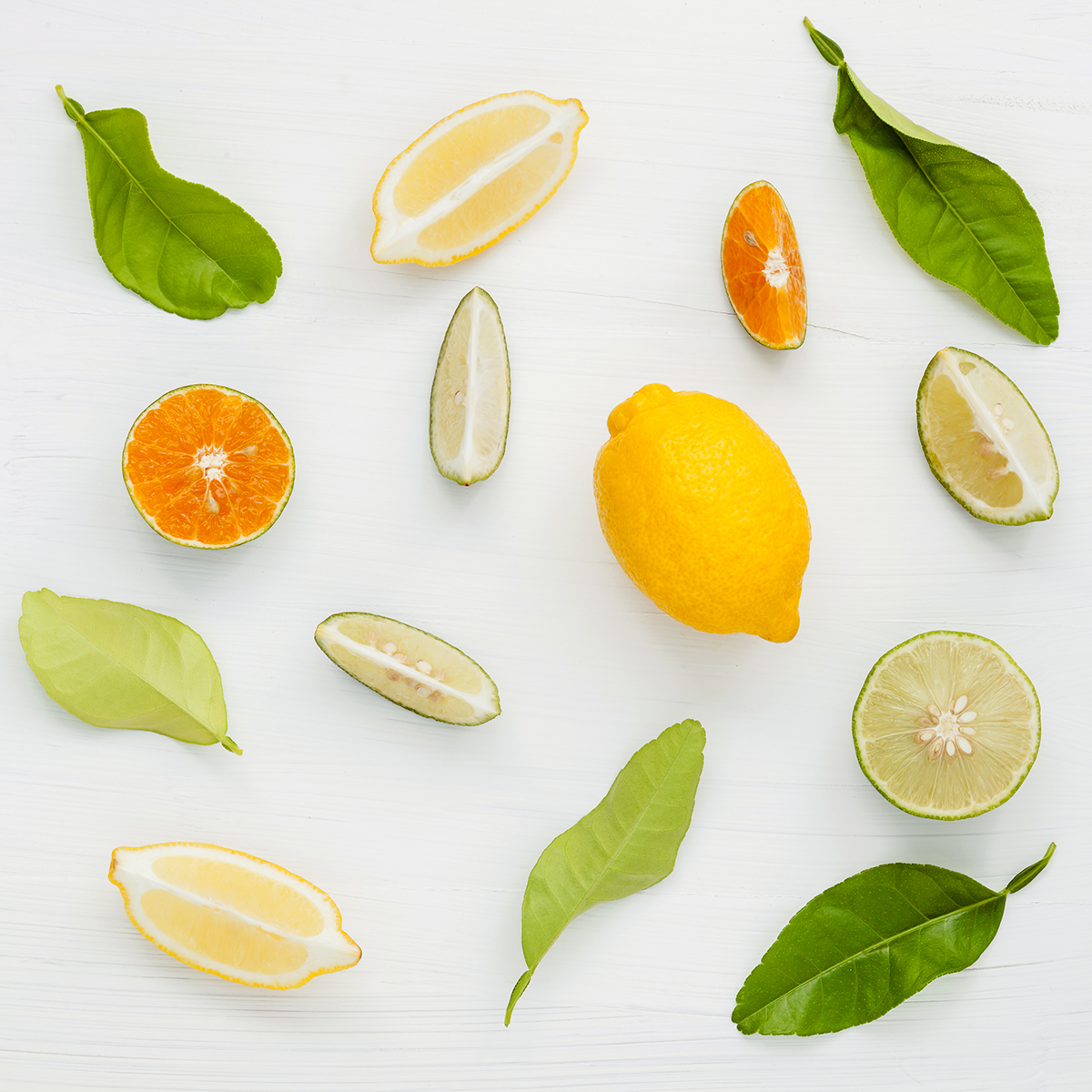 Mixed fresh citrus fruits and leaves background. Fresh lemons, lemon slice ,lime and orange on white wooden table with flat lay.