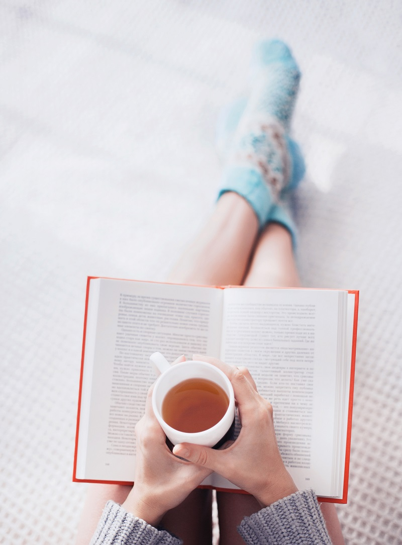 Close-up of female hands holding teacup in front of opened book