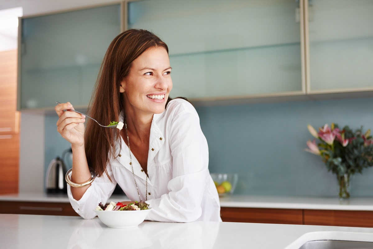 Woman having healthy breakfast and looking away with smile