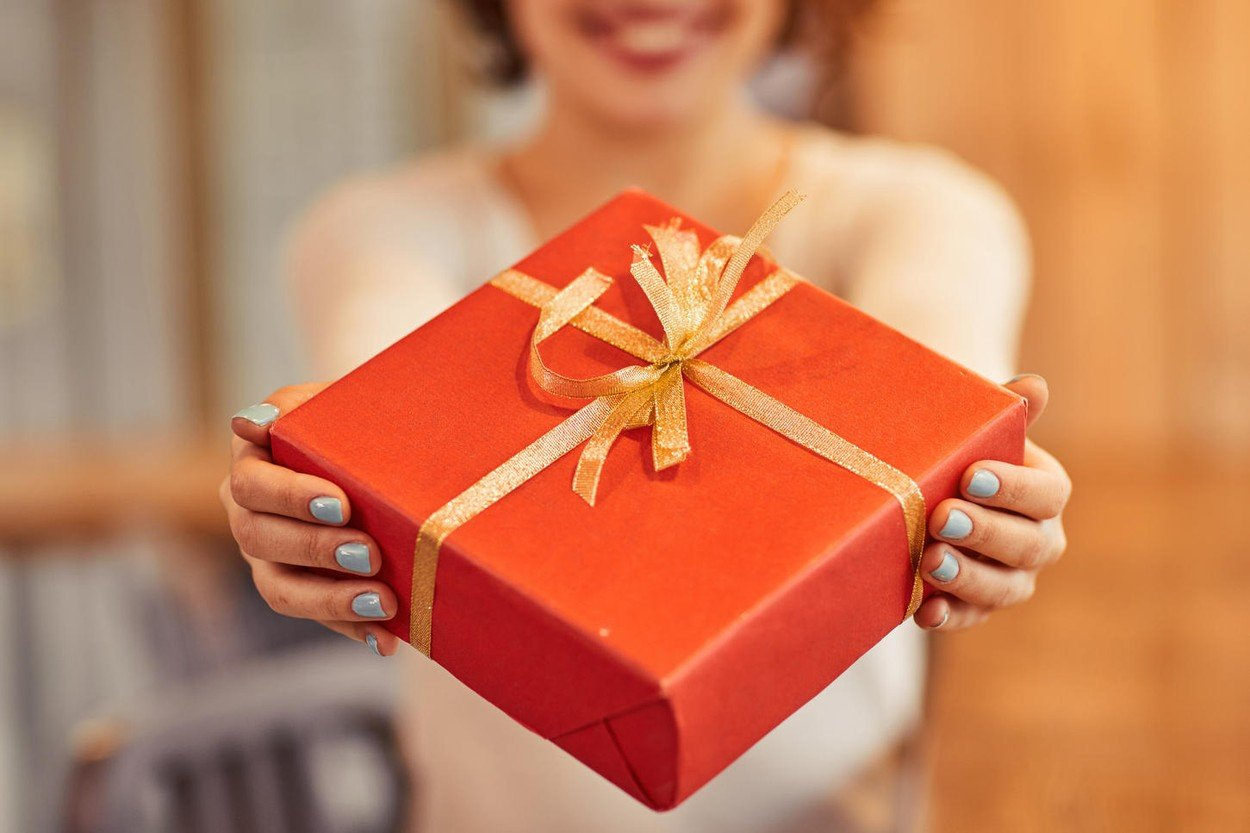My congratulation. Close up of present in hands of pleasant woman holding it and giving to you while smiling, Image: 280229710, License: Royalty-free, Restrictions: , Model Release: yes, Credit line: Profimedia, Alamy