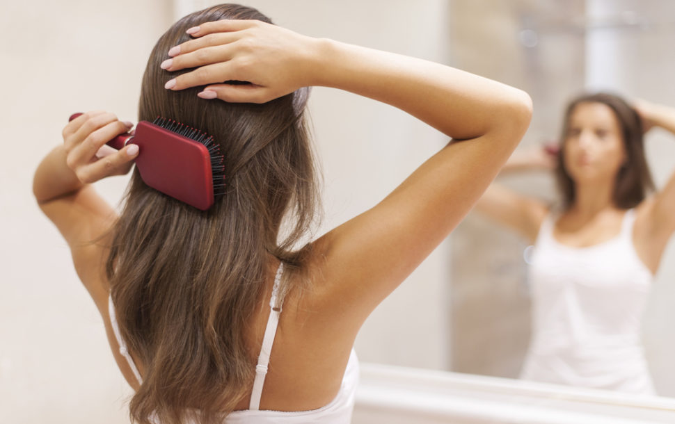 Young woman brushing healthy hair in front of a mirror