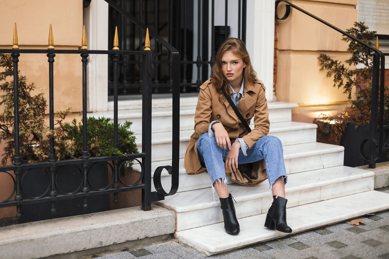 Young attractive woman in trench coat and jeans thoughtfully looking in camera sitting on little stairs spending time on cozy city street