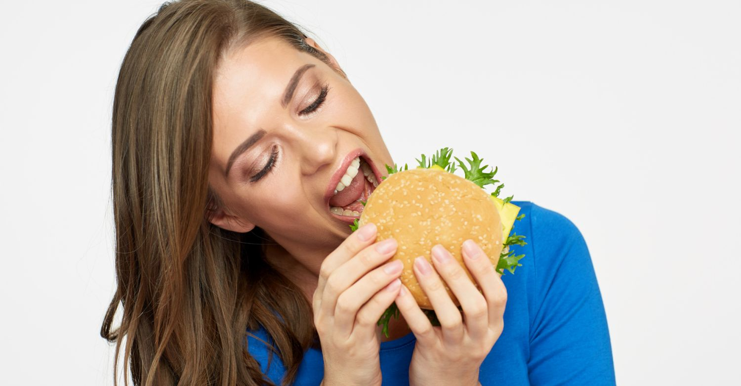 Look of real hunger of young woman eating big burger. Isolated portrait.