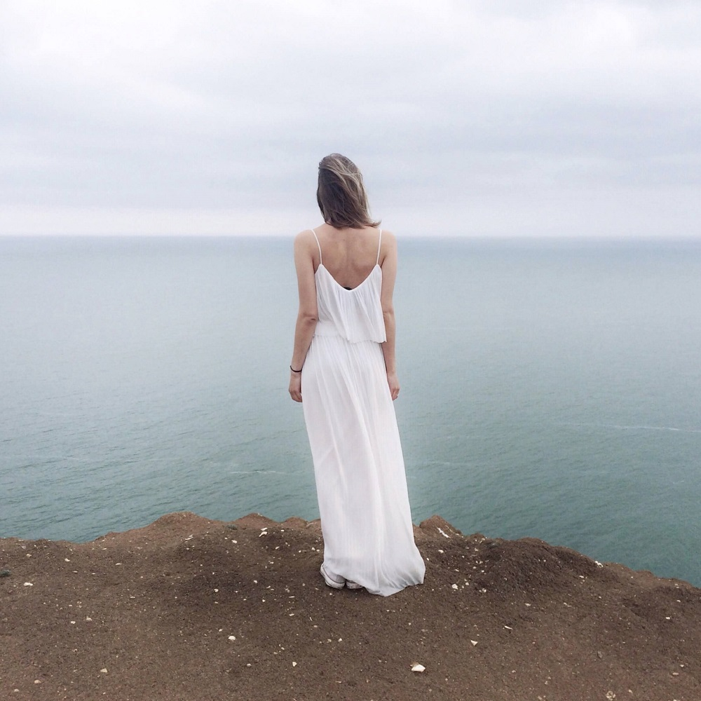 woman-in-white-spaghetti-strap-dress-standing-on-cliff-1030901