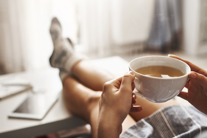 Cup,Of,Tea,And,Chill.,Woman,Lying,On,Couch,,Holding